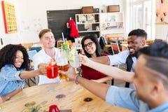Amis faisant tinter des verres avec des boissons au restaurant Images libres de droits
