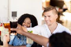 Amis faisant tinter des verres avec des boissons au restaurant Photo libre de droits