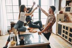 Amis faisant tinter des verres avec du vin à la partie de pizza Images stock