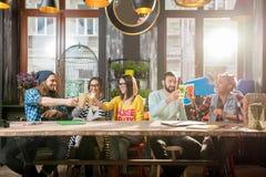 Amis faisant tinter des verres dans le café moderne Images libres de droits