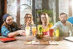 Amis faisant tinter des verres dans le café moderne Photographie stock libre de droits
