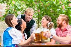 Amis faisant tinter des verres dans le jardin de bière Image libre de droits