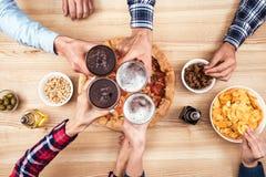 Amis faisant tinter des verres de bière Photographie stock libre de droits