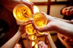 Amis faisant tinter des verres de bière au bar ou à la barre Image stock