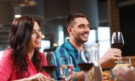 Amis faisant tinter des verres de vin au restaurant Photographie stock