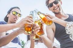 Amis faisant tinter la bière Images libres de droits