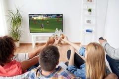 Amis faisant tinter la bière et observant le jeu de football Photographie stock