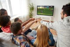 Amis faisant tinter la bière et observant le jeu de football Photo stock