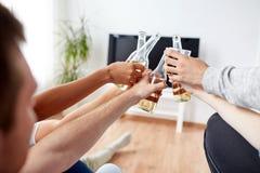Amis faisant tinter la bière et regardant la TV à la maison Images stock