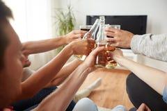 Amis faisant tinter la bière et regardant la TV à la maison Photo libre de droits