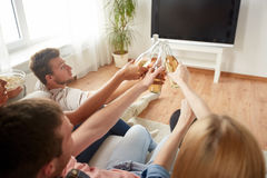 Amis faisant tinter la bière et regardant la TV à la maison Photos libres de droits