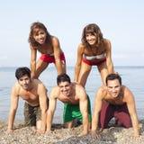Amis faisant un château sur la plage Photographie stock libre de droits