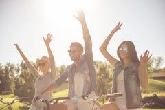 Amis faisant un cycle en parc Images libres de droits