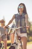 Amis faisant un cycle en parc Photos libres de droits