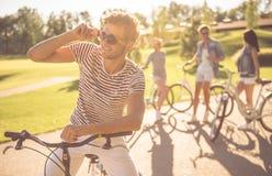 Amis faisant un cycle en parc Image libre de droits