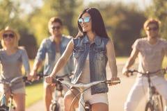 Amis faisant un cycle en parc Photographie stock