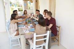 Amis faisant un pain grillé à un dîner sur un patio, Ibiza Image stock