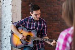 Amis fille et homme jouant la guitare acoustique Image libre de droits