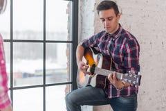 Amis fille et homme jouant la guitare acoustique Photographie stock libre de droits