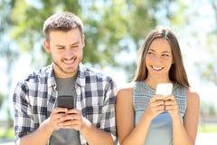 Amis flirtant avec des téléphones dans une première date Image stock
