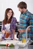 Amis flirtant dans la cuisine Photos stock