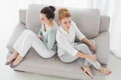 Amis féminins malheureux ne parlant pas après argument sur le divan Photo libre de droits