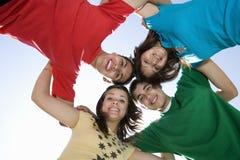Amis formant un petit groupe contre le ciel Photographie stock
