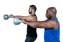 Amis forts soulevant des kettlebells ensemble Photos stock