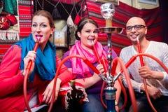 Amis fumant un narguilé dans le salon de shisha Photos libres de droits