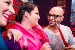 Amis fumant un narguilé dans le salon de shisha images libres de droits