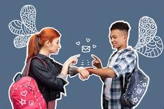 Amis gais à l'aide des montres intelligentes et envoyant des messages entre eux Photos libres de droits