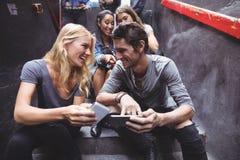 Amis gais à l'aide des téléphones portables sur des étapes à la boîte de nuit Photos stock