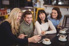 Amis gais à l'aide du comprimé numérique tout en se reposant au café Image stock