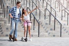 Amis gais à l'aide du scooter Photo stock