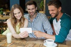 Amis gais à l'aide du téléphone portable tout en se reposant par la table Photo stock