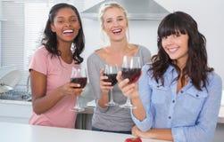 Amis gais appréciant des verres de vin rouge Image stock