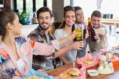 Amis gais appréciant la bière avec la nourriture au restaurant Photographie stock