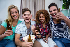 Amis gais appréciant la bière tout en regardant la rencontre à la maison Images libres de droits