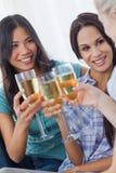 Amis gais appréciant le vin blanc ensemble Photo stock