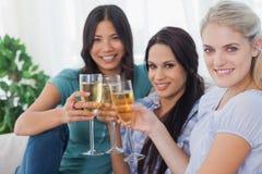Amis gais appréciant le vin blanc souriant ensemble à l'appareil-photo Photographie stock
