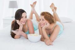 Amis gais avec à télécommande et maïs éclaté dans le lit Photographie stock