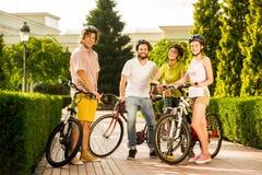 Amis gais avec des bicyclettes dehors Photos stock
