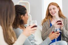 Amis gais avec des verres de vin appréciant une conversation à la maison Photographie stock