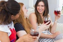 Amis gais avec des verres de vin appréciant une conversation Photographie stock