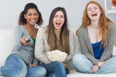 Amis gais avec la cuvette à télécommande et de maïs éclaté sur le sofa Images libres de droits