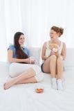 Amis gais avec les tasses de café et le bol de fruit dans le lit Images libres de droits
