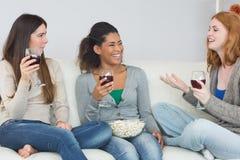 Amis gais avec les verres et le maïs éclaté de vin appréciant une conversation à la maison Photos stock