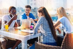 Amis gais ayant l'amusement au café Image libre de droits