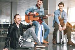 Amis gais ayant l'amusement avec la guitare Photo libre de droits