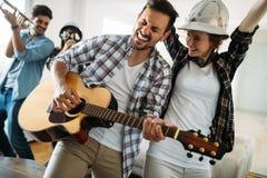 Amis gais ayant la partie ensemble et jouant des instruments Images stock